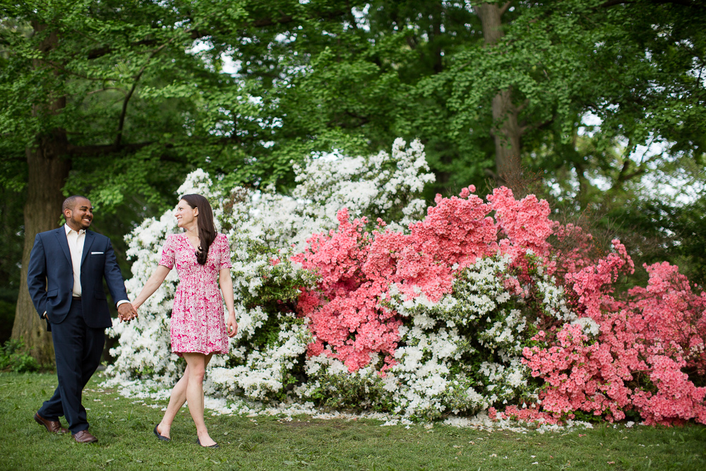 Walking through Central Park for an engagement shoot | Pink and white flowers | New York City Engagement Photographer | Megan Rei Photography