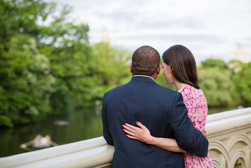 Standing on the Bow Bridge and looking down at the water | Engagement pictures in Central Park, New York City