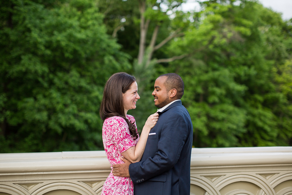 Engaged couple cuddling up on the Bow Bridge during their Central Park engagement photos