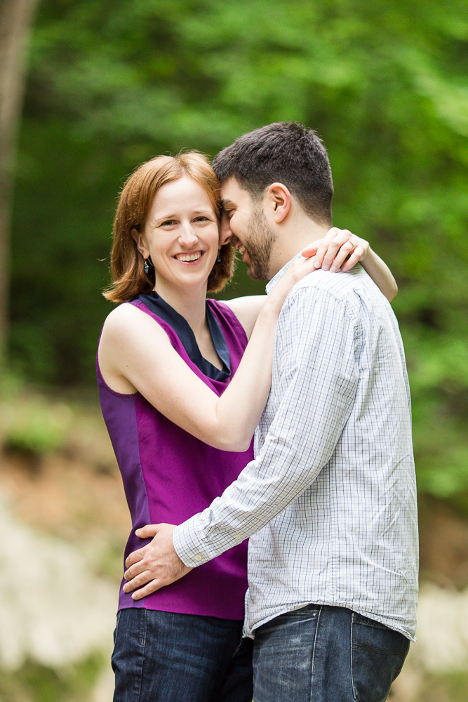 Smiling engaged couple during engagement session in the woods