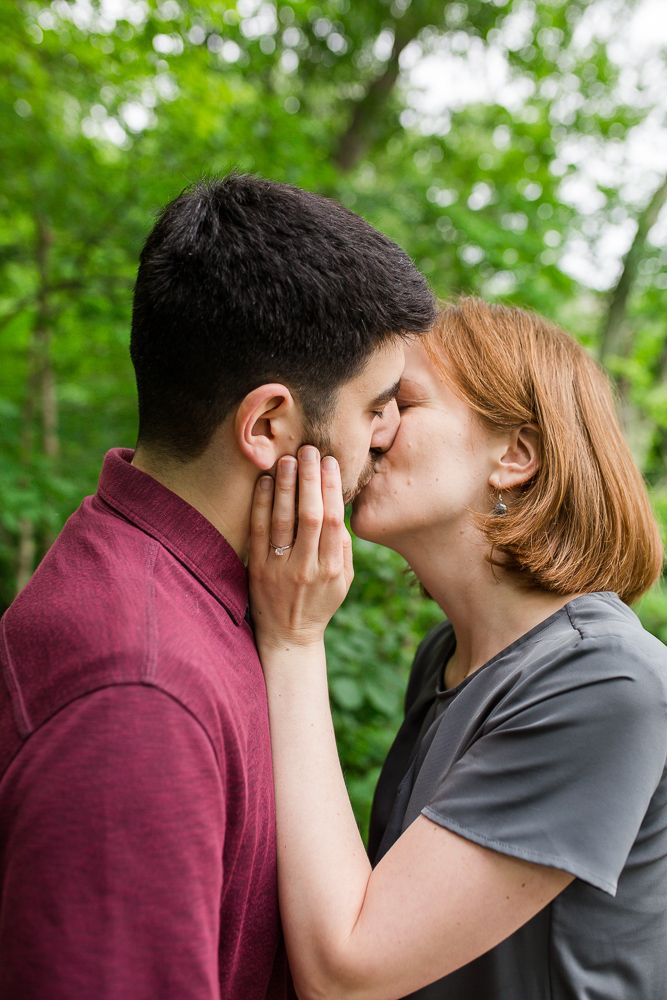 Couple kisses during engagement photos in the woods