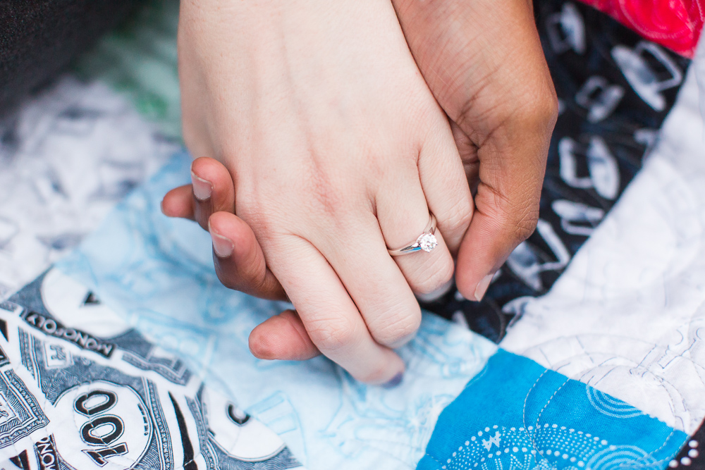 Holding hands and showing off the engagement ring