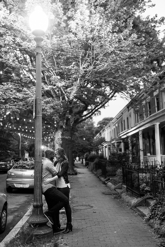 Cuddling up under the lamppost during a nighttime engagement session in DC | DC Engagement Photographer