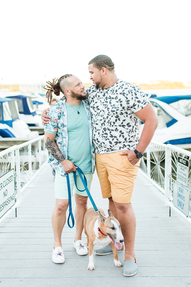 Same-sex couple with their dog on the dock at the Alexandria waterfront