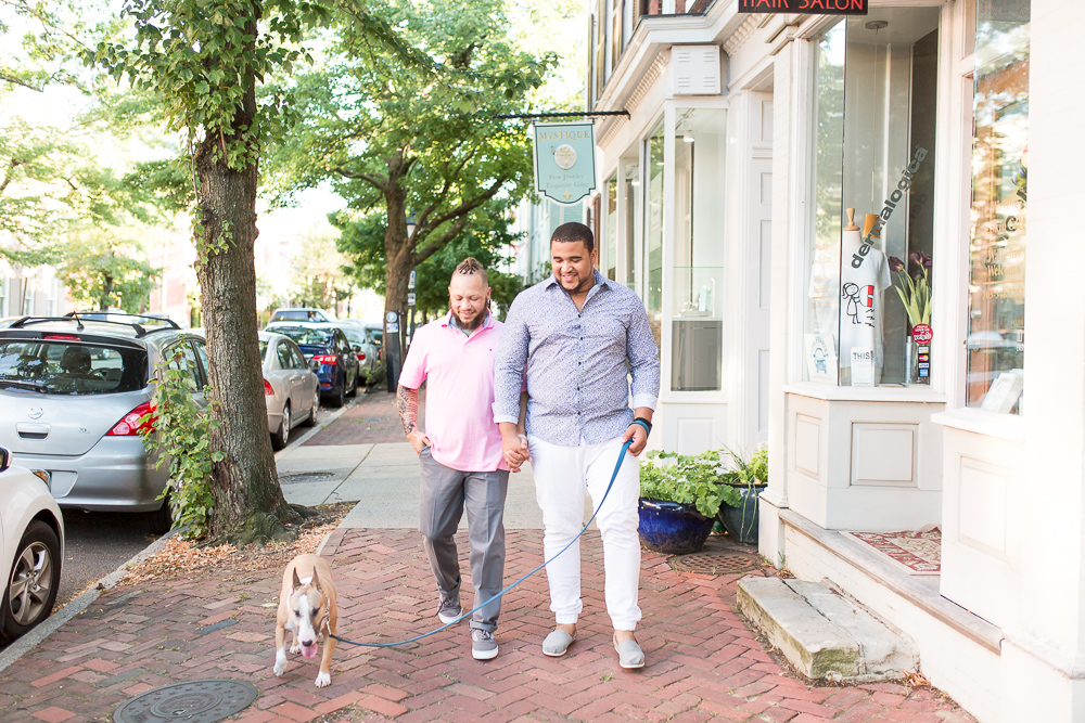 Gay couple holding hands and walking down the streets of Old Town Alexandria with their dog