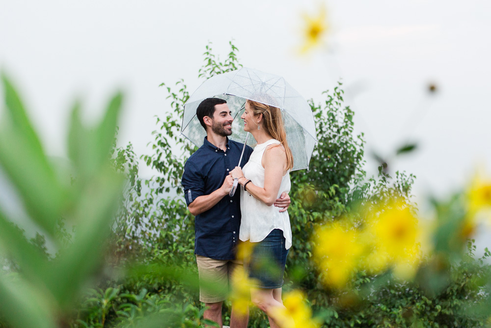 Happy engaged couple, smiling despite the rain during their engagement session