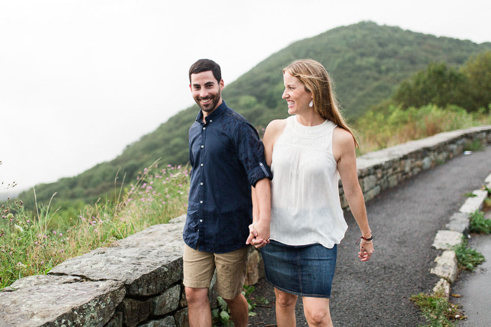 Engaged couple laughing in the rain on Skyline Drive   Shenandoah National Park engagement session
