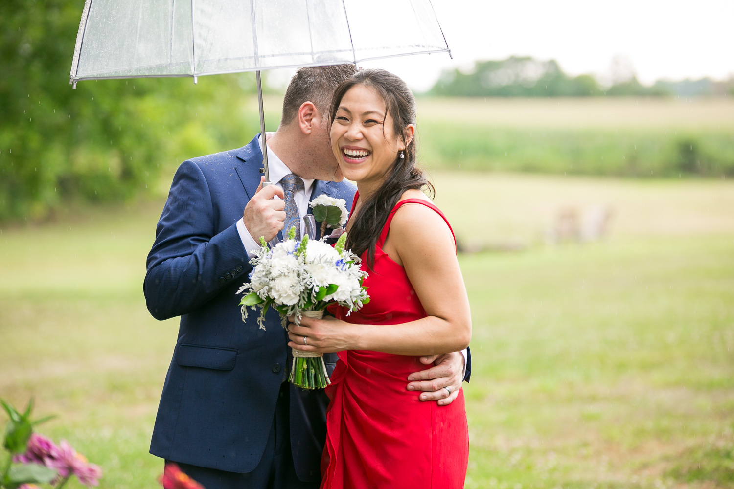 Smiling bride and groom on rainy wedding day