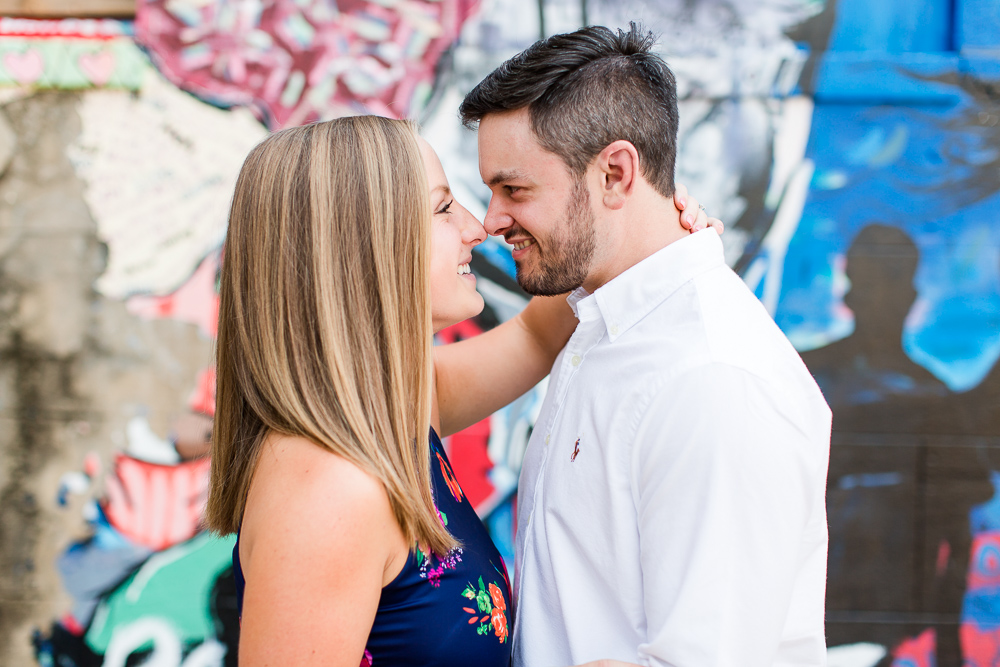 Sweet engaged couple posing in front of street art