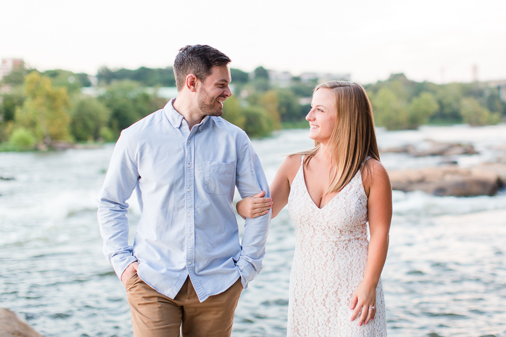 Candid photos of engaged couple walking along the James River in RVA