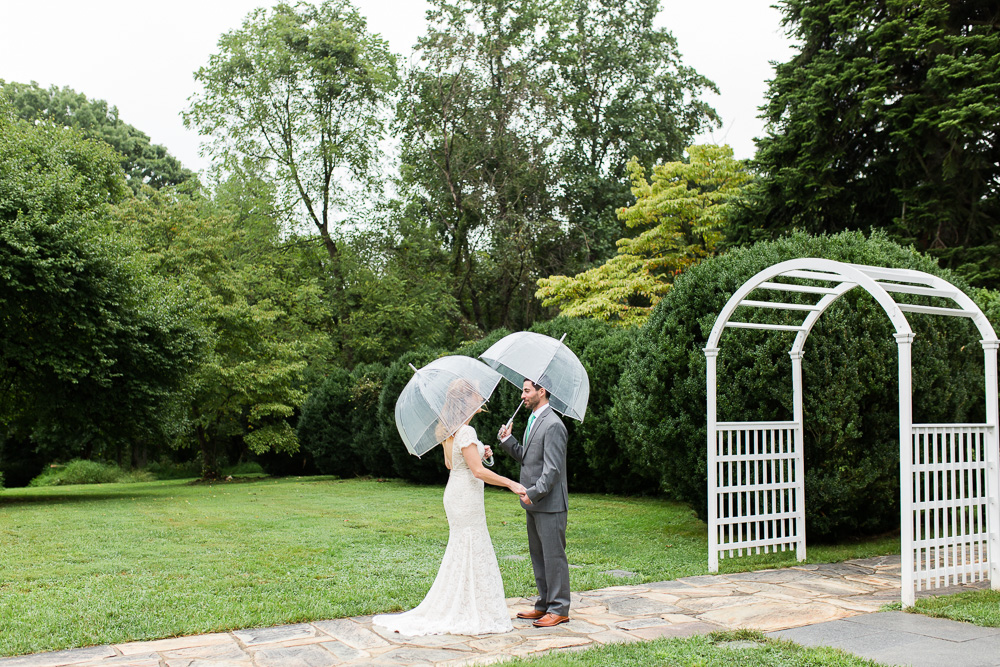 Bride and groom standing in the rain with umbrellas