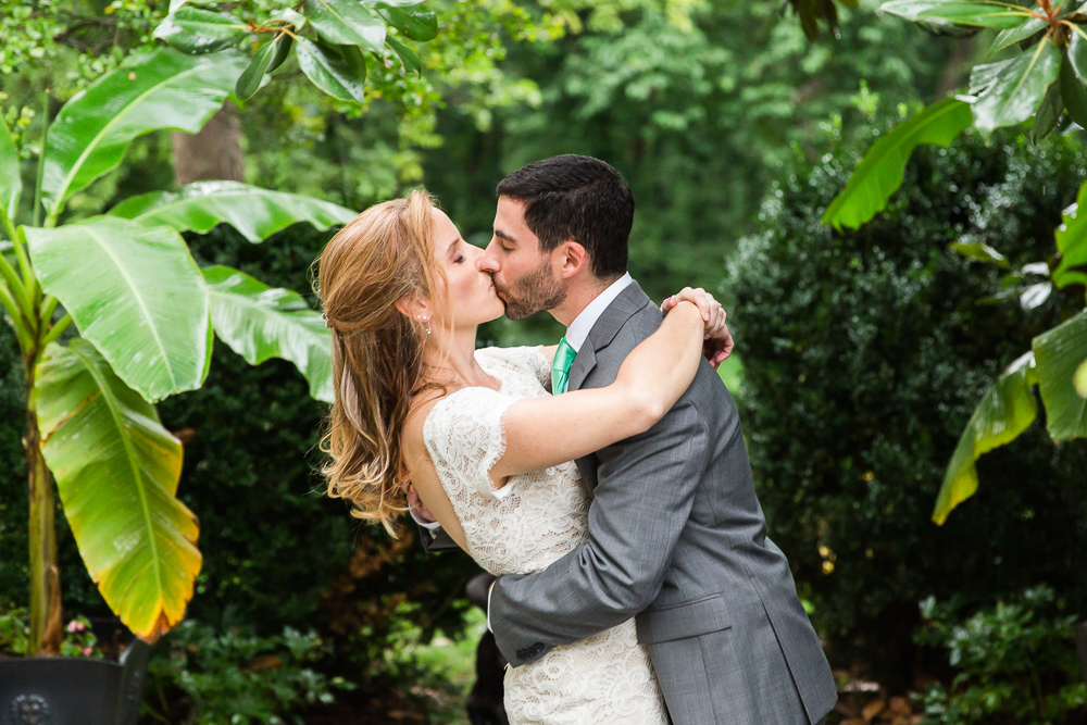 Bride and groom kiss on the magnolia garden deck at Rust Manor House