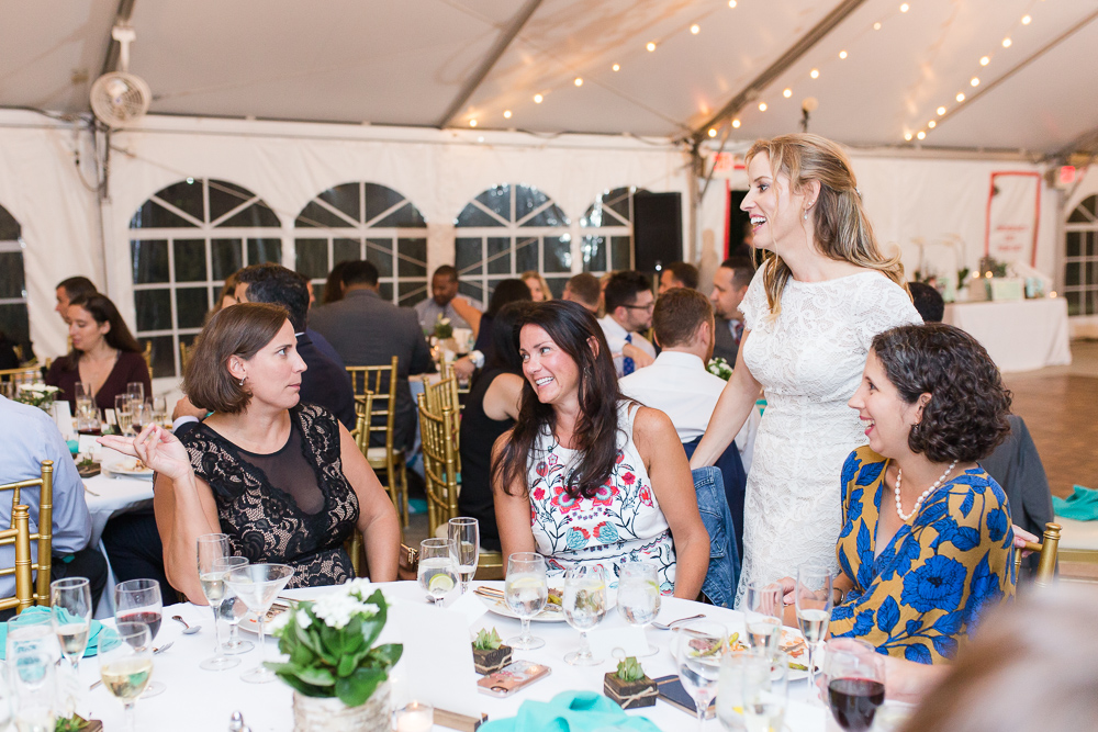 Candid shot of bride chatting with wedding guests during reception in the Rust Manor House tent