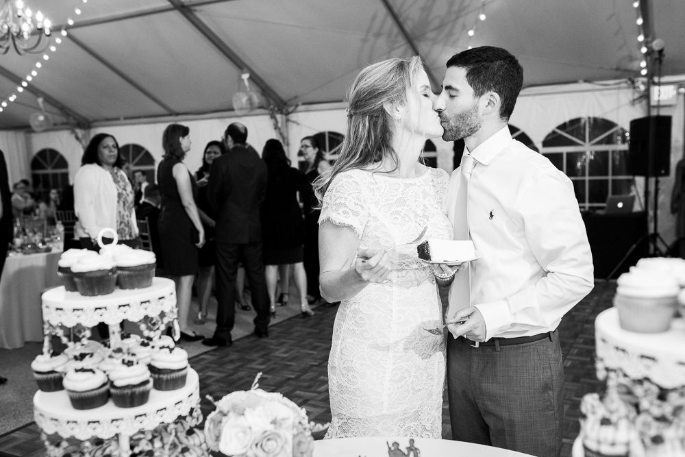 Bride and groom kiss after the cake cutting | Rust Manor House wedding photos