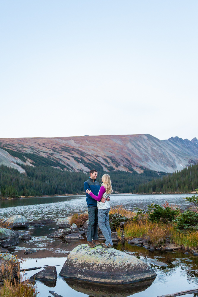 Engaged couple on a boulder in Long Lake in the Brainard Lake Recreation Area