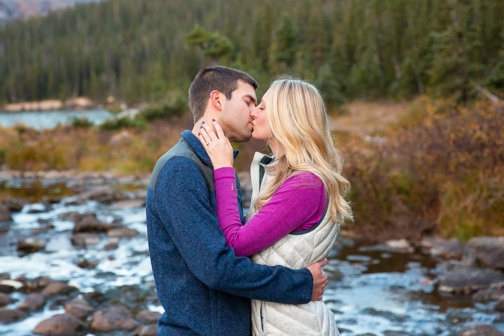 Engaged couple kisses during their hike