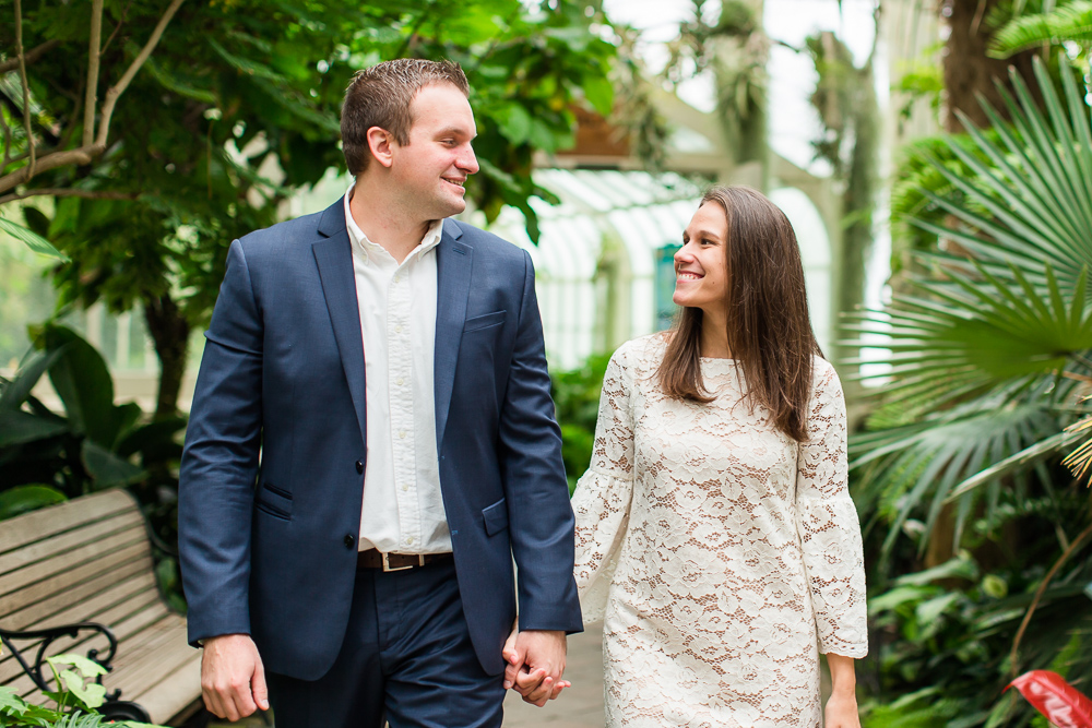 Engaged couple holding hands as they walk through the Buffalo Botanical Gardens | Best engagement photo locations in Buffalo, NY