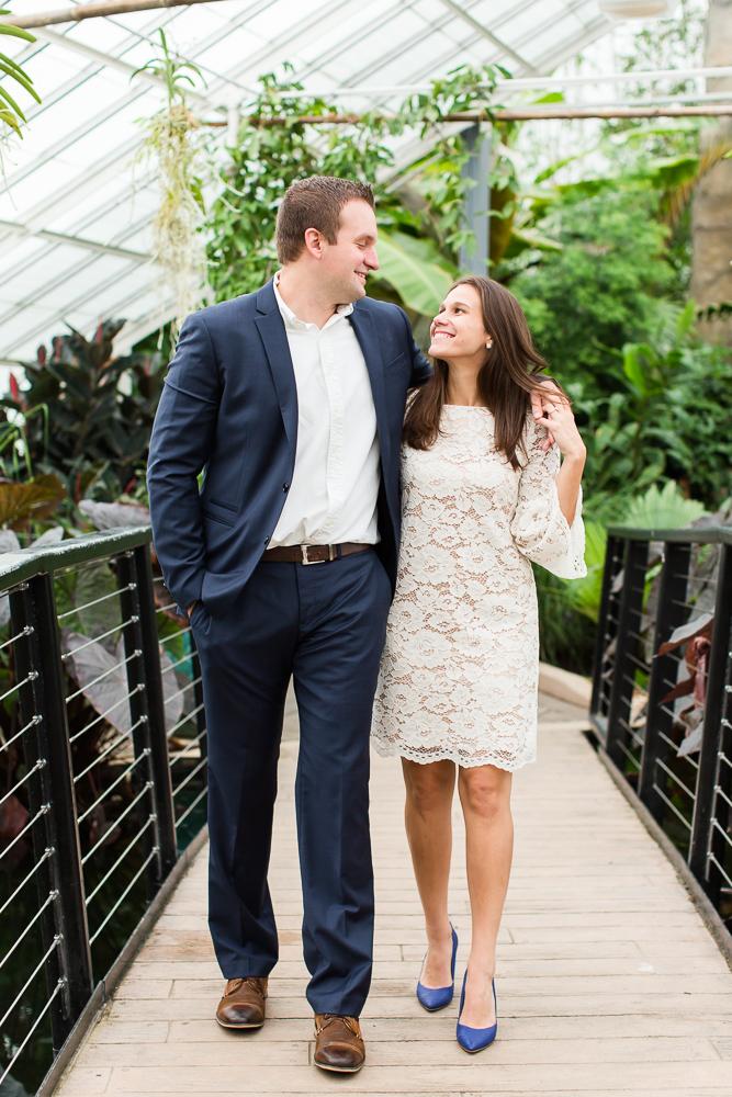 Engagement photo walking across a bridge in the botanical gardens