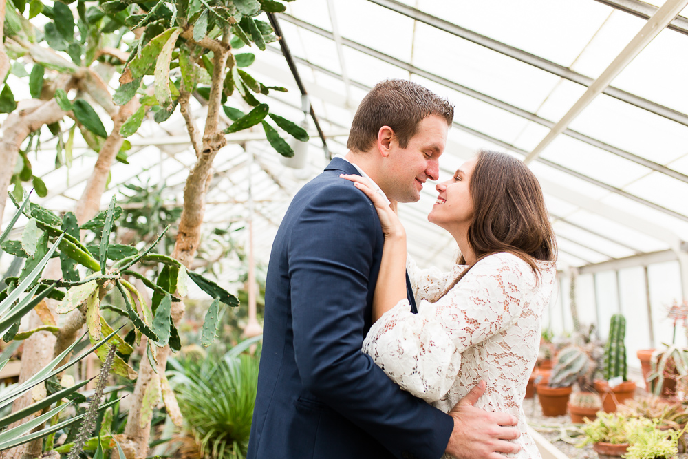 Happy couple cuddling during their engagement session in the greenhouse | Buffalo Wedding Photographer