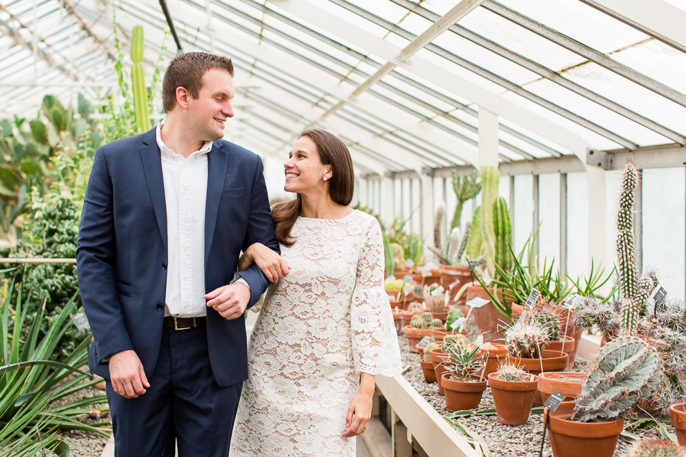 Candid engagement photograph of smiling couple looking at each other as they walk through the greenhouse | Buffalo Wedding Photography