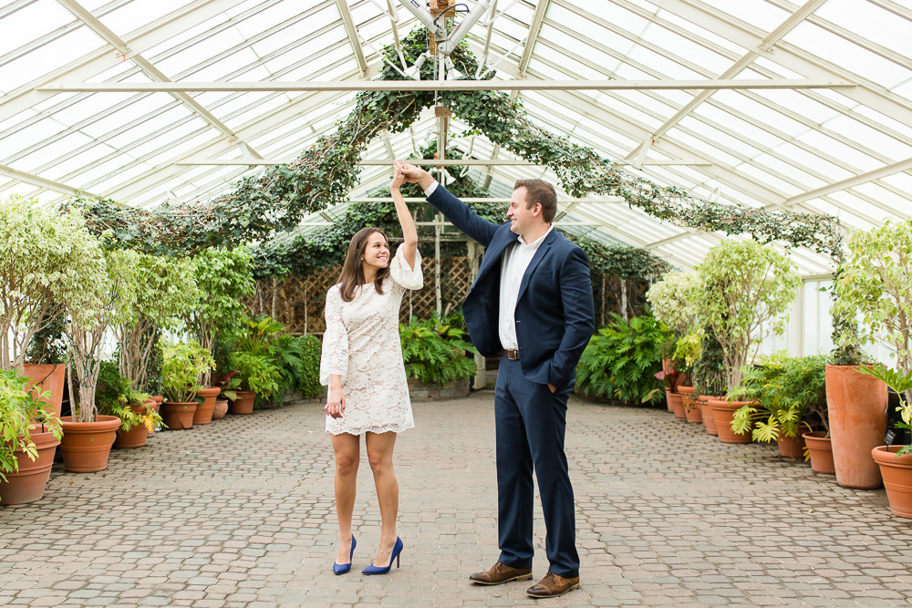 Dancing in the greenhouse during an engagement session at the Buffalo and Erie County Botanical Gardens