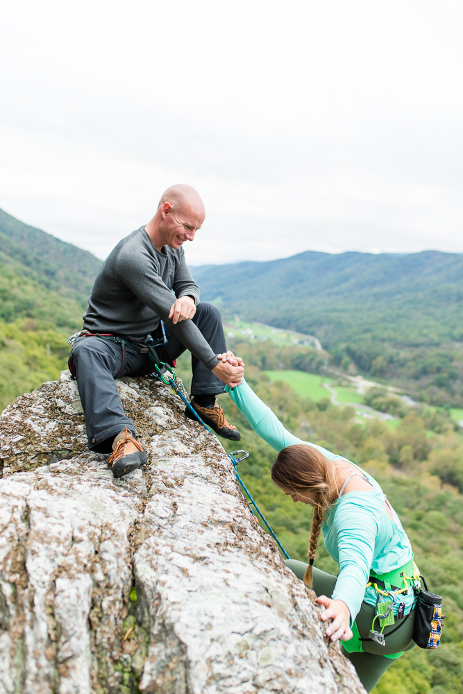 Engaged couple reaching the summit of Seneca Rocks during a rock climbing engagement session | Best Northern Virginia engagement photography