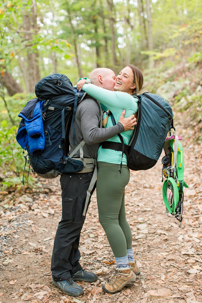 Couple laughing as they hug during a backpacking engagement shoot at Seneca Rocks, West Virginia