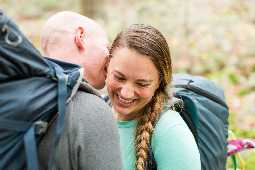 Engaged couple cuddling on trail during their backpacking and rock climbing engagement shoot at Seneca Rocks