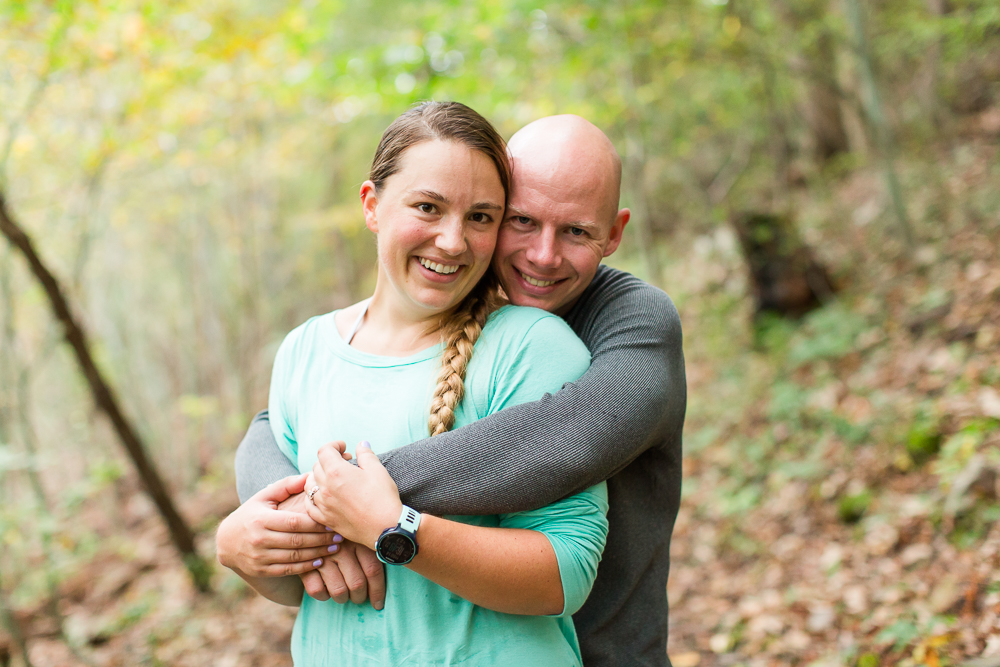 Smiling at the camera for outdoorsy engagement pictures in the woods
