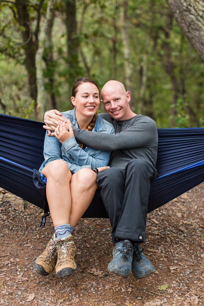 Smiling couple in their hammock in the woods during an adventure engagement shoot | Northern Virginia adventure engagement photography