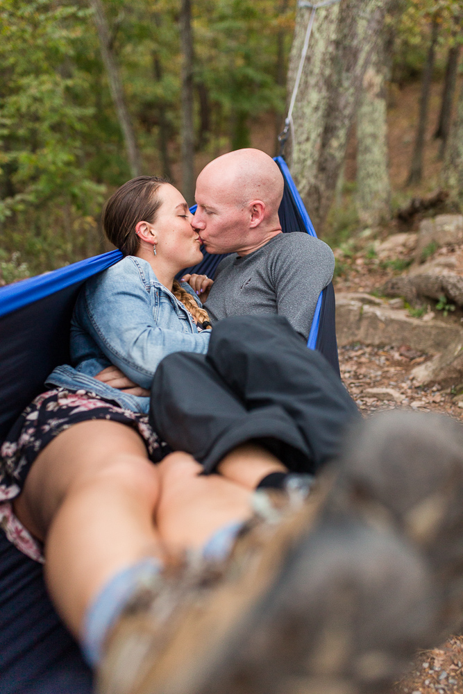 Engaged couple kisses while cuddling in a hammock during their hiking and rock climbing engagement session