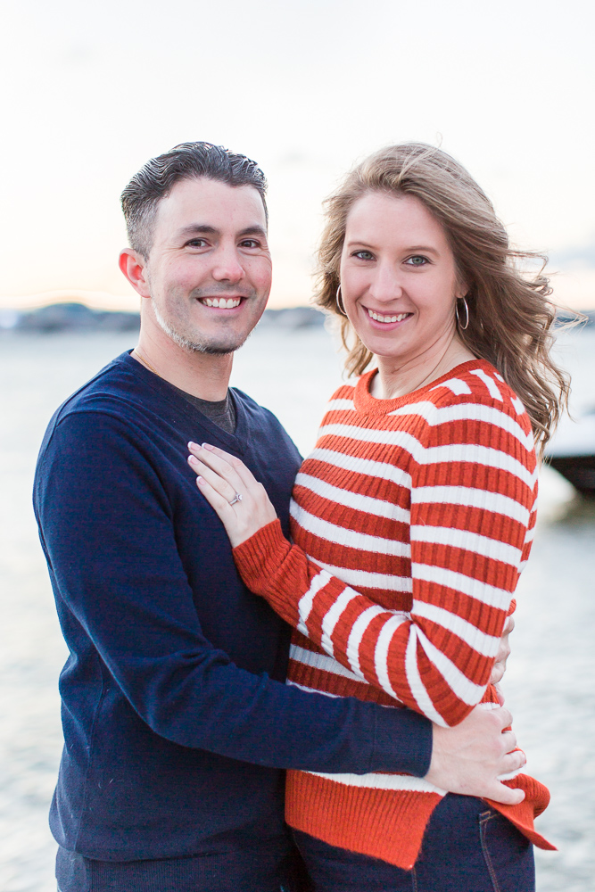 Happy engaged couple smiling at the camera during a sunrise engagement session