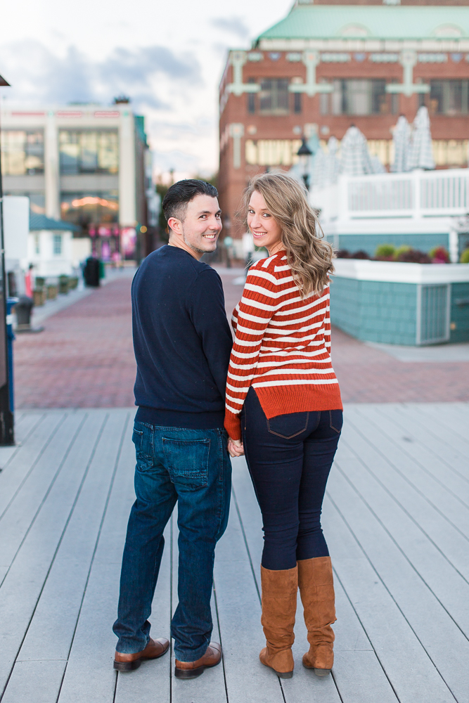 Engagement picture of couple looking over their shoulders at the Old Town Alexandria Waterfront