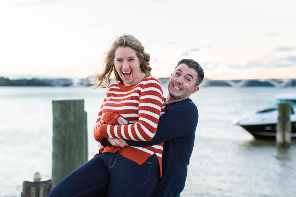 Engaged couple goofing around during their engagement session at the Alexandria waterfront