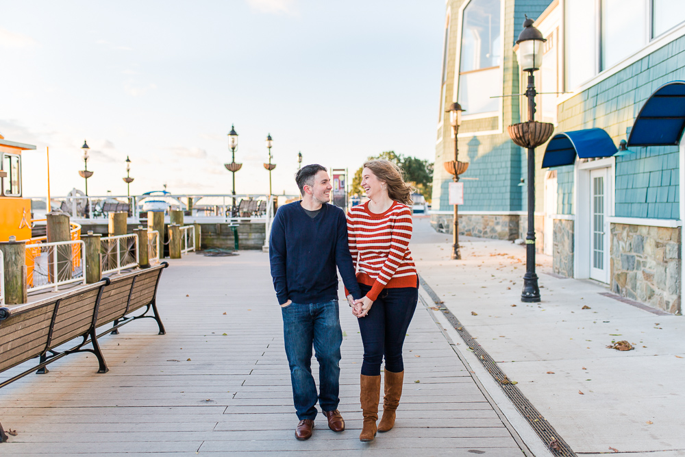 Happy couple laughing at holding hands as they walk along the Old Town Alexandria waterfront   Old Town Engagement Photos