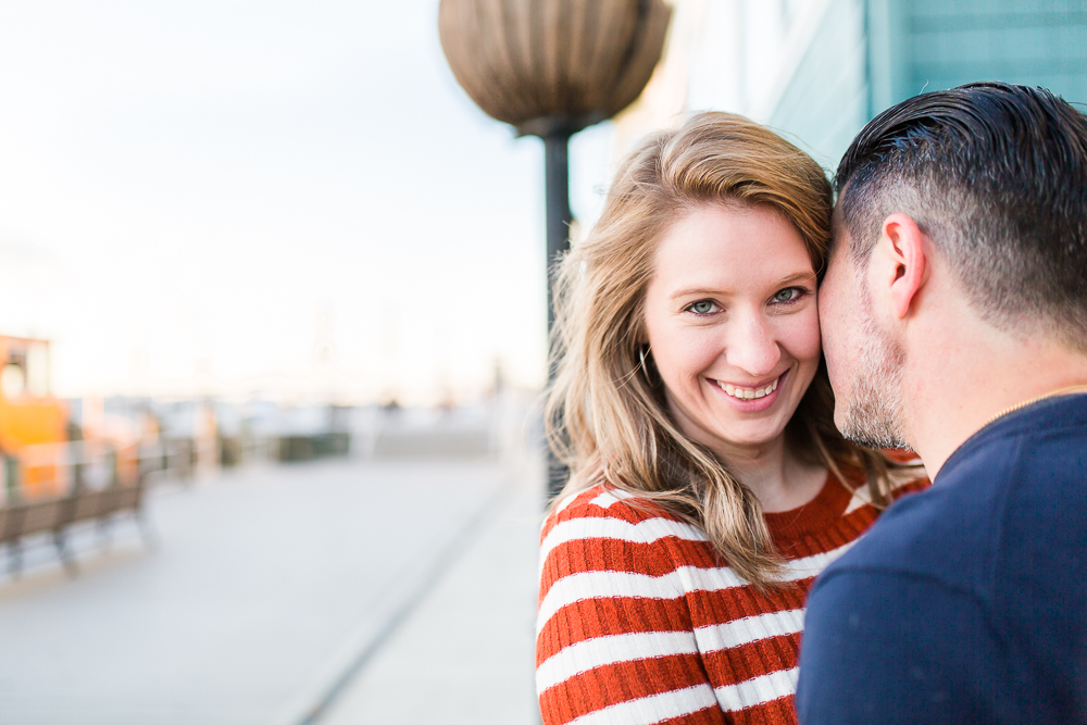 Candid engagement photography at the Old Town Alexandria waterfront   Bride smiling at the camera while groom cuddles her