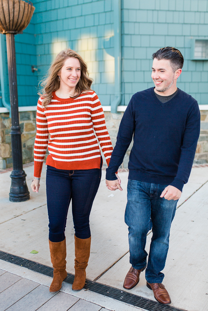 Happy engaged couple laughing as they walk by the Chart House in Alexandria, Virginia