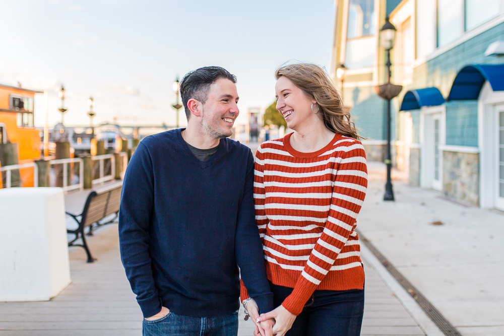 Sweet picture of engaged couple walking hand-in-hand along the boardwalk in Old Town Alexandria