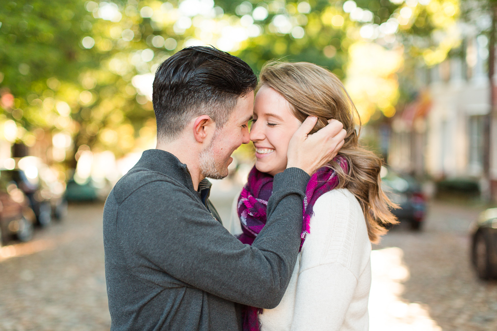 Engaged couple leaning in for a kiss on Prince Street in Old Town Alexandria   Alexandria Engagement Pictures