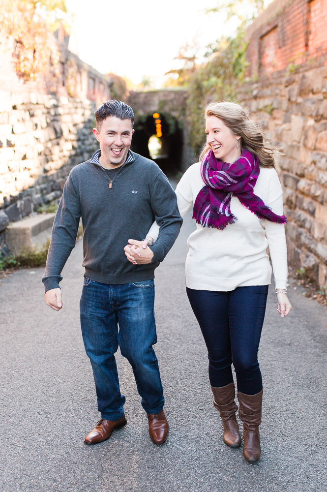 Candid engagement picture of couple laughing as they walk through the Wilkes Street Tunnel in Old Town Alexandria