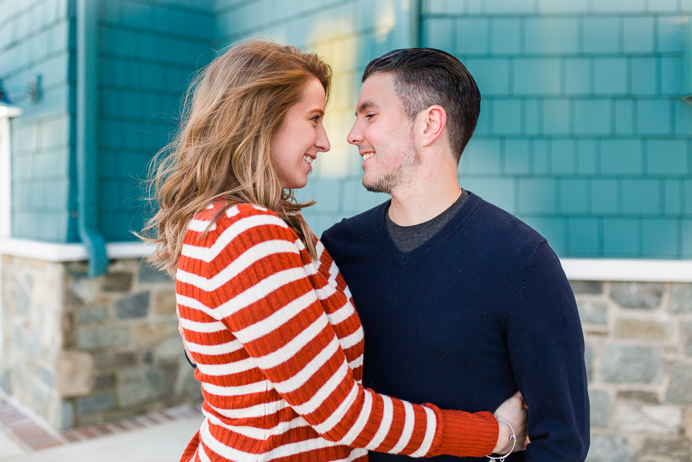 Engagement pictures by the teal wall of the Chart House in Old Town Alexandria   Old Town Engagement Photographer