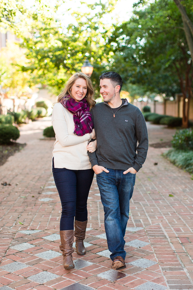 Engaged couple walking arm in arm along the brick sidewalk in Old Town Alexandria