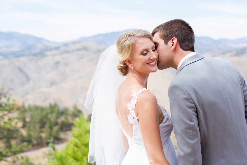 Groom kissing bride on the cheek with Colorado mountains in the background