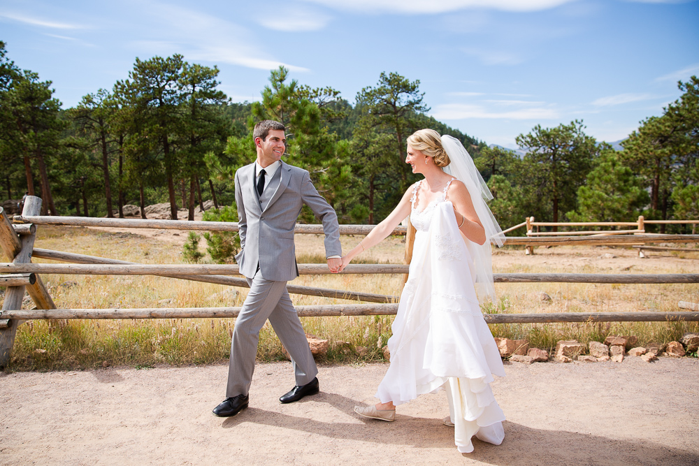 Husband and wife holding hands as they walk along the trail at Lookout Mountain Park | Wedding pictures in Golden, Colorado