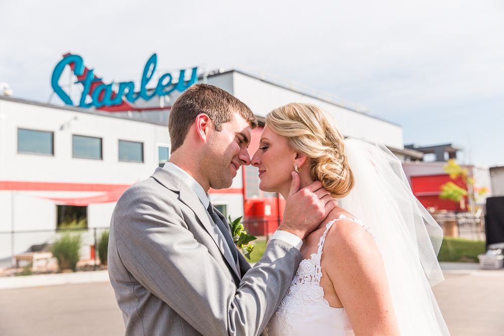 Bride and groom going in for a kiss in front of The Hangar at Stanley Marketplace | Aurora, CO Wedding Venue