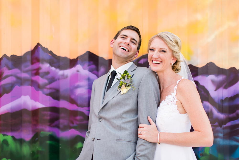 Bride and groom laughing in front of the mountain mural at Stanley Marketplace | Colorado Wedding Photography
