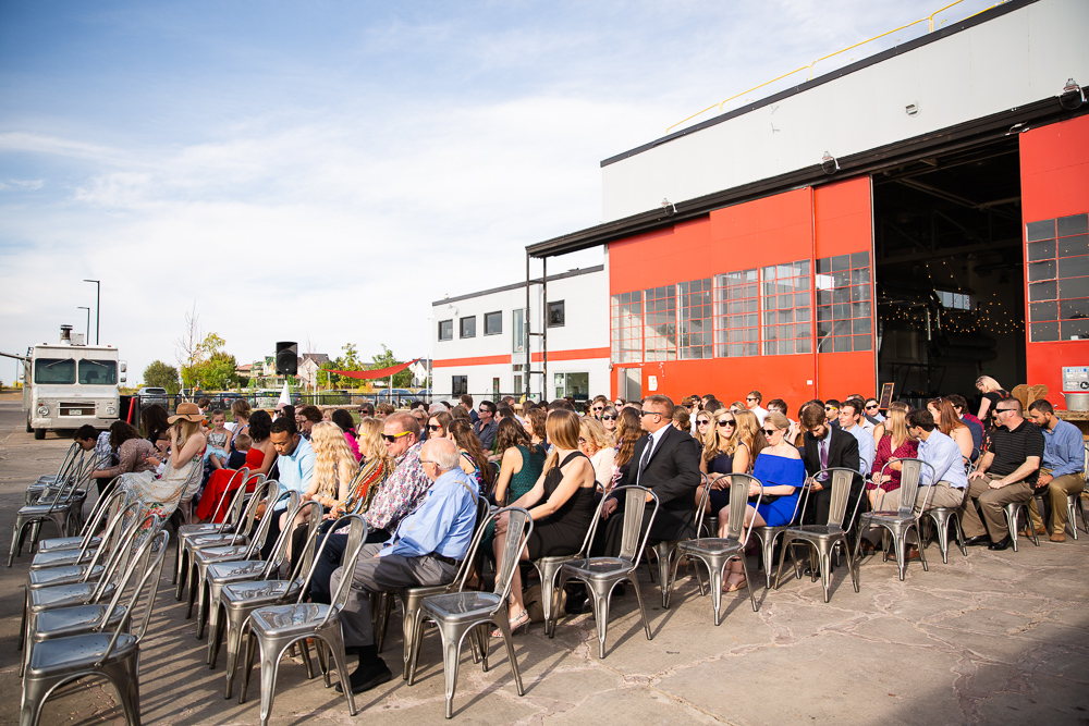 Wedding guests seated and waiting for the ceremony to start at The Hangar at Stanley Marketplace, Aurora, Colorado
