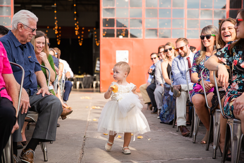 Flower girl walking down the aisle in front of the big red doors
