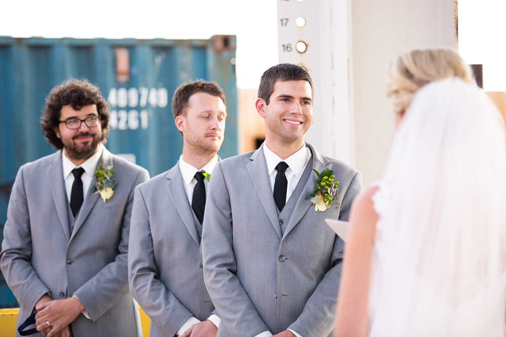 Candid photo of groom smiling during the wedding ceremony at Stanley Marketplace