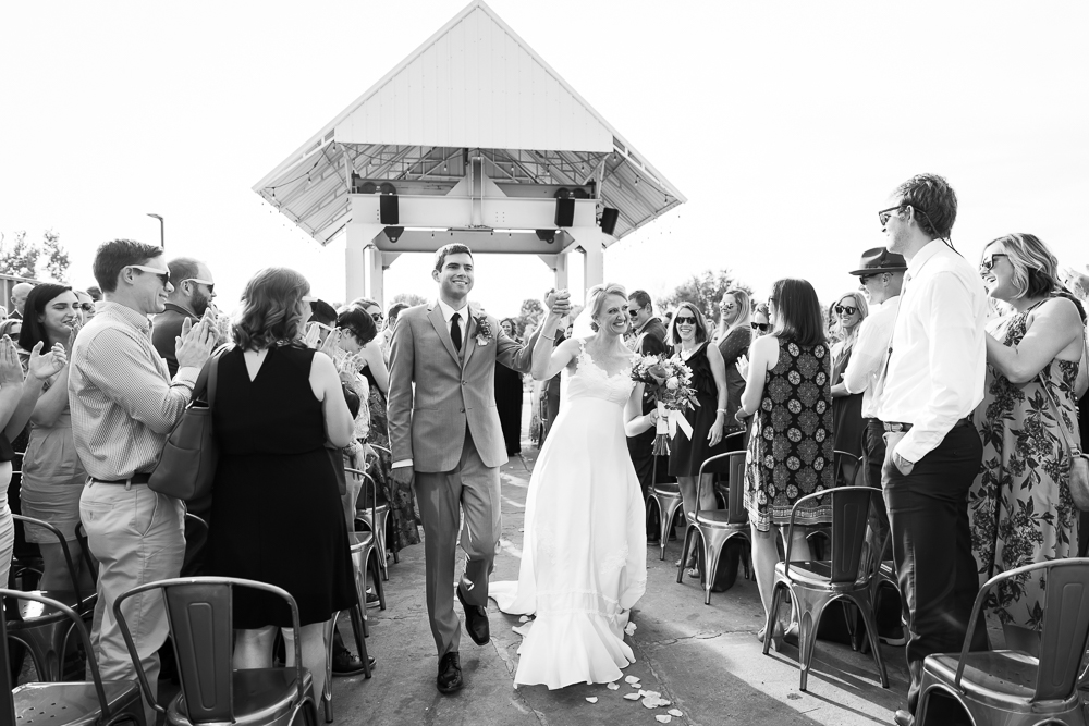 Happy husband and wife at the end of their wedding ceremony at Hangar at Stanley Marketplace | Best wedding venues in Denver, CO